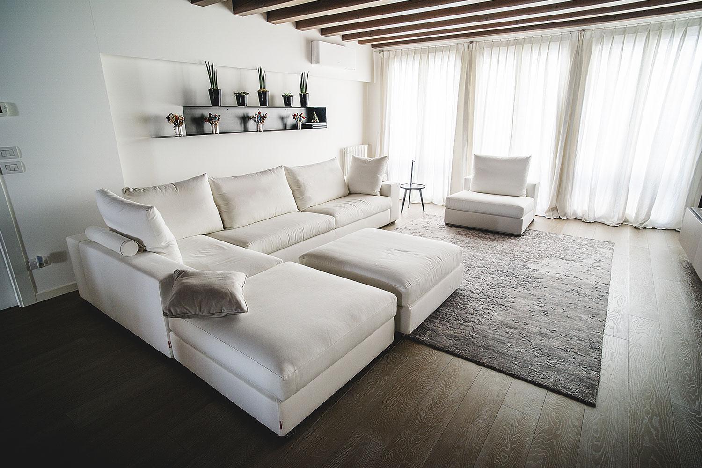 Luminoso salotto con divano bianco e mensola minimalista